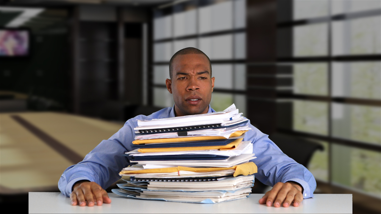 Video of Frustrated HR Manager with Paperwork Piled on His Desk
